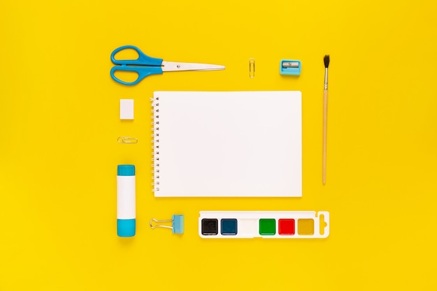 Top view of modern white, blue, yellow office desktop with school supplies and stationery on table around empty space for text. back to school concept flat lay with mockup