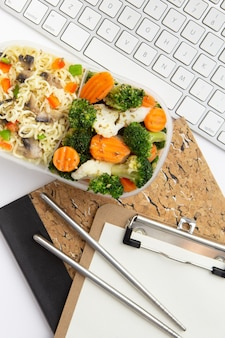 Top view modern workplace arrangement with food close-up