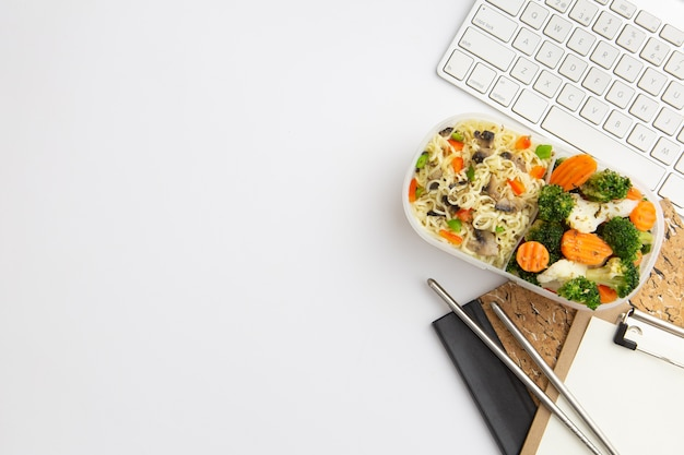Top view modern workplace arrangement with food and copy space