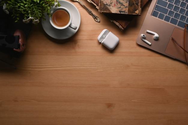 Современное рабочее место взгляда сверху с компьтер-книжкой, тетрадью, беспроводным наушником, кофейной чашкой и заводом на деревянной предпосылке.