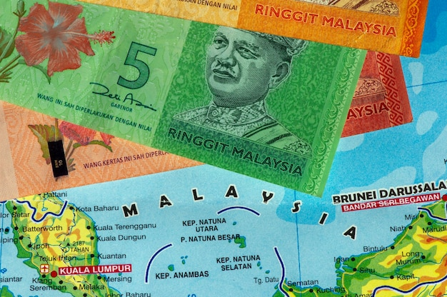 Top view of money, banknote of ringgit malaysia and the malaysia map for background. business, finance, economy and investment concept