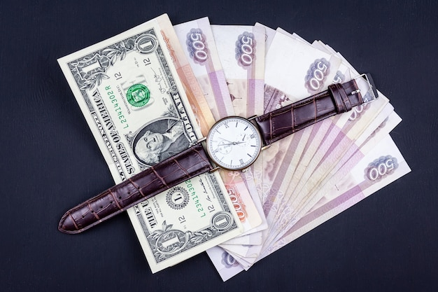 Top view of money pile with watch