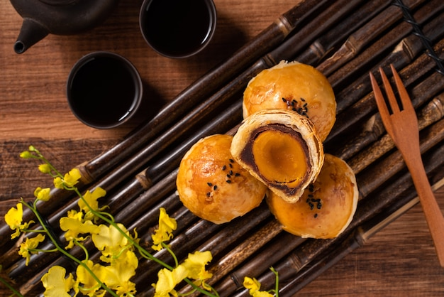 Top view of moon cake yolk pastry, mooncake for mid-autumn festival holiday on wooden table background
