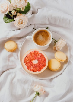 Top view of morning coffee with grapefruit and macarons