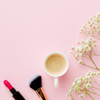 Top view morning coffee with lipstick and brush