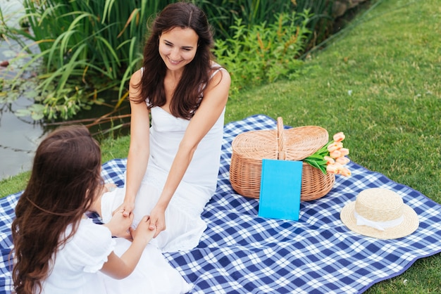 Top view mother and daughter holding hands at picnic