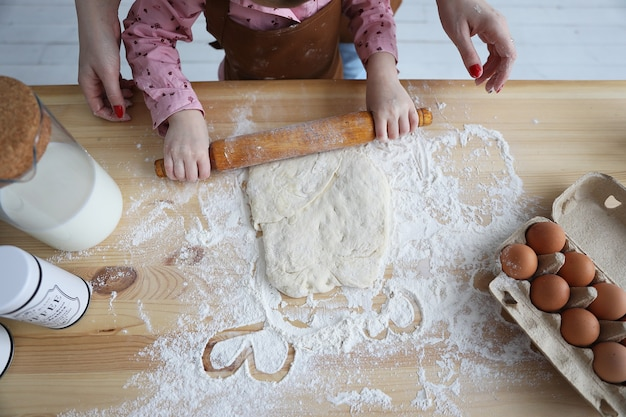 Top view of mother and daughter in the kitchen drawing hearts on the flour