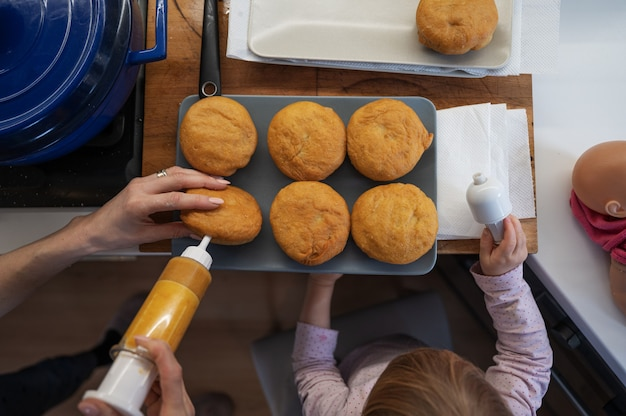 Top view of a mother filling freshly fried vegan doughnuts with jam, with her toddler daughter helping her.
