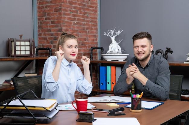 La vista dall'alto del team di gestione motivato seduto al tavolo è arrivata alla negoziazione nella sala riunioni in ufficio