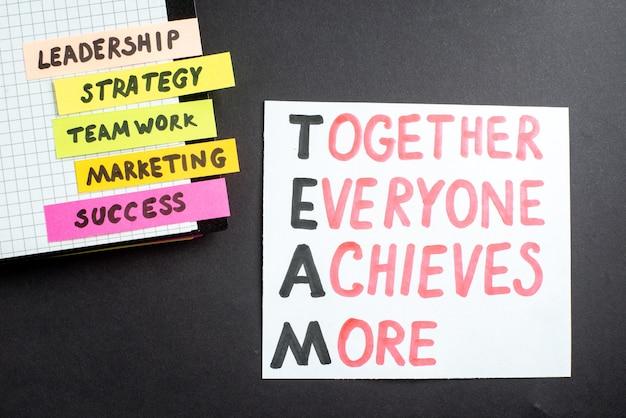 暗い背景にメモ帳付きのトップビューモチベーションビジネスノートビジネスワーク成功ジョブリーダーシップ戦略チームワークマーケティングオフィスチーム