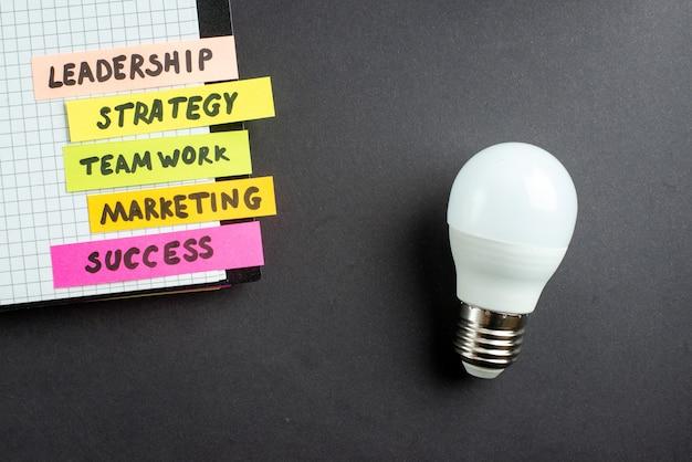 어두운 배경에 메모장으로 상위 뷰 동기 부여 비즈니스 노트 비즈니스 작업 성공 작업 전략 팀워크 마케팅 사무실 리더십