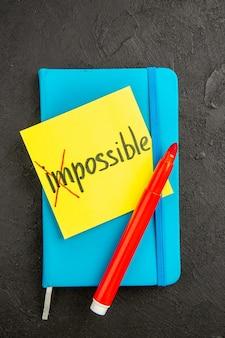 Nota motivazionale vista dall'alto con quaderno blu su superficie scura che scrive taccuino quaderno foto penna a colori scuola presenta