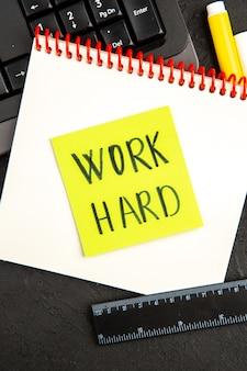 Nota motivazionale vista dall'alto con tastiera e matite su superficie scura