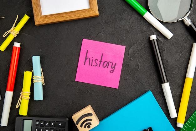 学校の色のペンのコピーブックのメモ帳の現在の写真を書く暗い表面に鉛筆でトップビューの動機付けのメモ