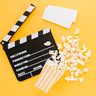 Top view movie clapperboard with tasty popcorn