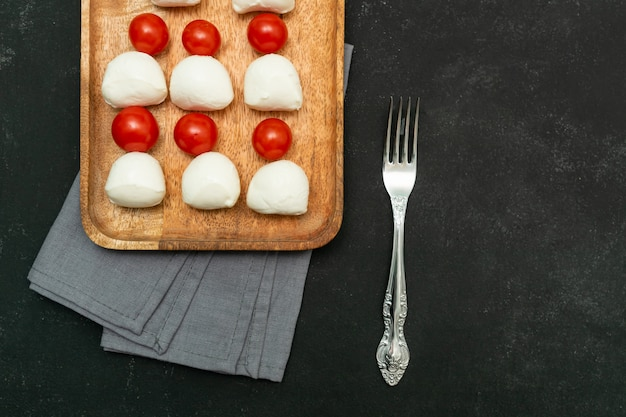 Top view of mozzarella cheese and cherry tomatous on wooden plate. italian antipasti with copy space.