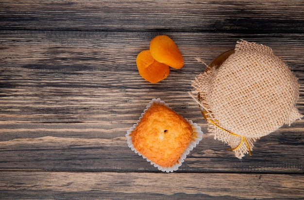 Top view of muffin with dried apricots and peach jam in a glass jar on rustic wood with copy space