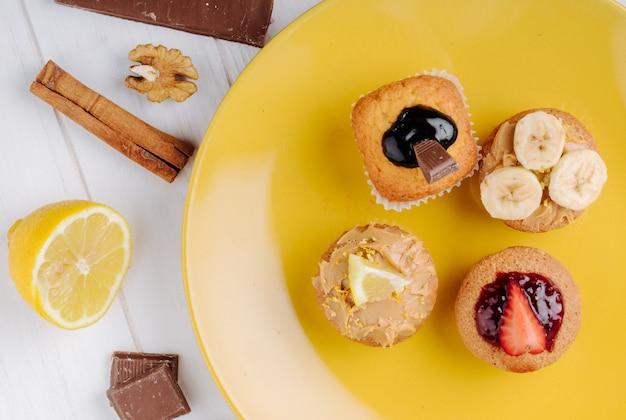 Вид сверху кексы с бананами, клубникой, шоколадом и лимоном на желтой тарелке с корицей