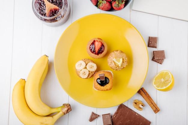 Вид сверху кексы с бананами, клубникой, шоколадом и лимоном на желтой тарелке