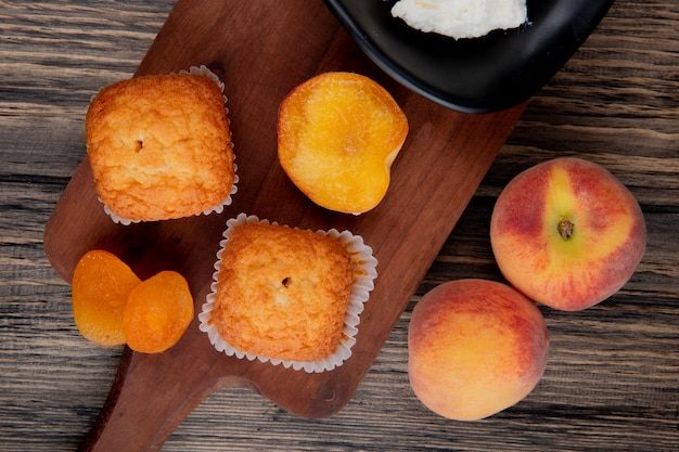 Top view of muffins with dried apricots on wood cutting board and fresh peaches on rustic
