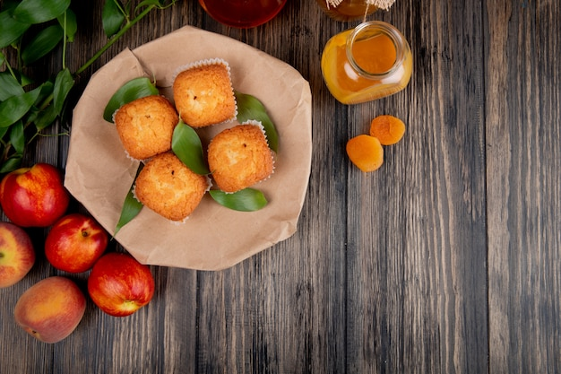 Top view of muffins with green leaves on craft brown paper with fresh ripe nectarines and peach jam in a glass jar on rustic wood with copy space