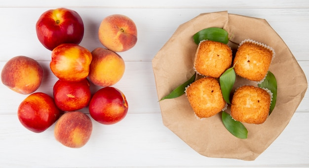 Top view of muffins with green leaves on craft brown paper with fresh ripe nectarines on white rustic wood