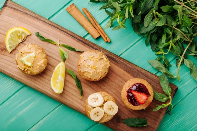 Top view muffins with strawberries banana and lemon on a board with cinnamon and mint