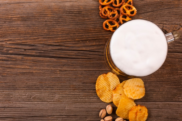Top view of mug and snacks on wooden background