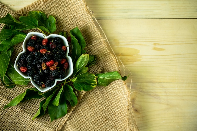 Top view of mulberries in bowl with leaves on sackcloth and wooden background with copy space