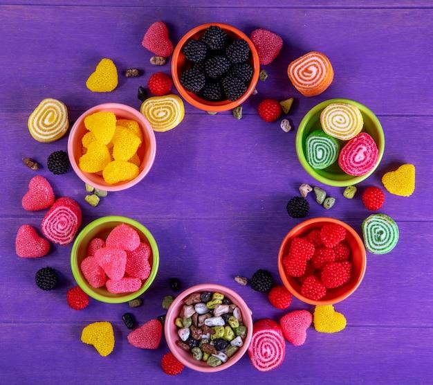 Вид сверху разноцветный мармелад с шоколадными камнями в блюдцах для варенья на фиолетовом фоне