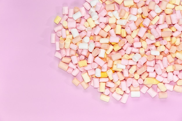 Top view on multi-colored marshmallows on a monochrome pink background