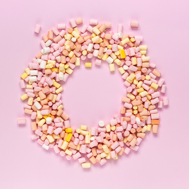 Top view of the multi-colored marshmallows which lies in the shape of a round frame with an area for text in the center on a monochrome pink background