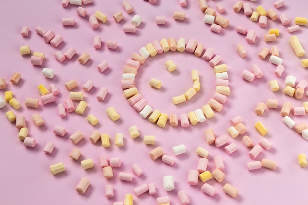 Top view of the multi-colored marshmallows which lies in the shape of a smiley or sun on a one-color pink background