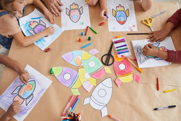 Top view of multi-ethnic group of kids drawing pictures of space rockets with crayons while enjoying art and craft class in pre school or development center