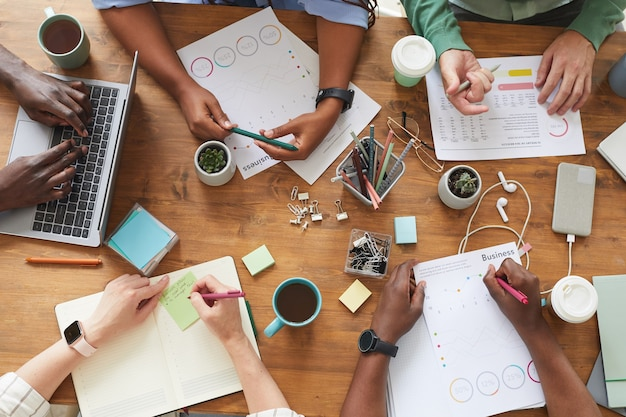Top view of multi-ethnic group of people working together at cluttered wooden table with coffee cups, mugs and stationary items, teamworking or studying concept