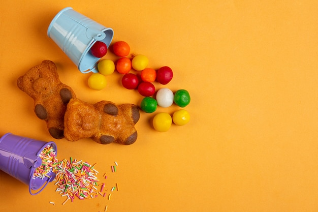 Top view of multicolor chocolate candies scattered from small bucket and sponge cakes in a shape of bear on yellow