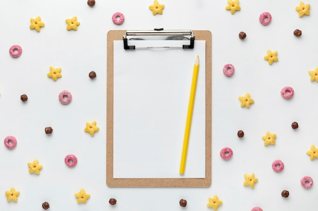 Top view of multicolored breakfast cereals in different shapes with notepad