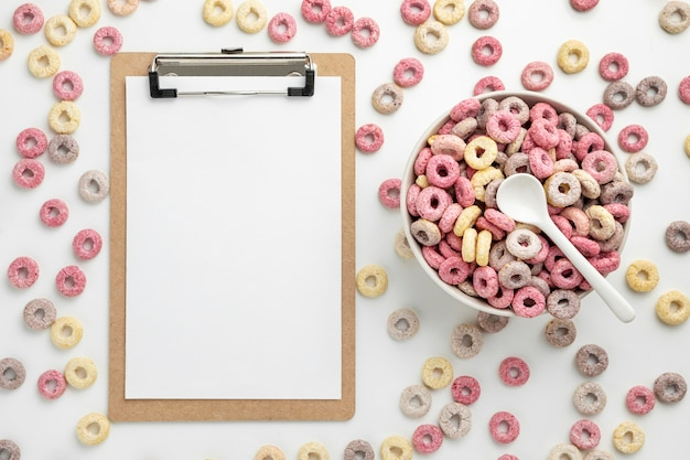 Top view of multicolored breakfast cereals with notepad