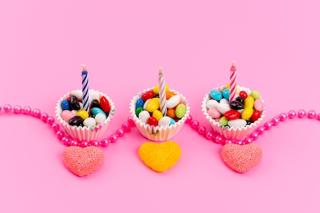 A top view multicolored candies inside white, paper packages along with candles and marmalade on pink, color rainbow sugar sweets