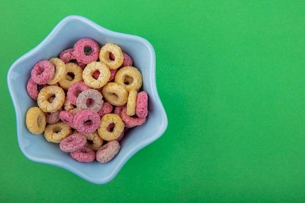 Vista dall'alto di cereali multicolori su una ciotola a forma di stella sulla superficie verde