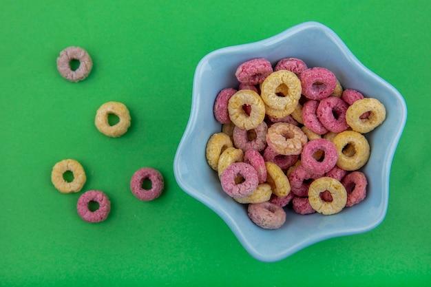 Vista superiore dei cereali multicolori su una ciotola a forma di stella con i cereali isolati su superficie verde