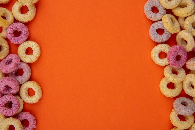 Top view of multicolored delicious and loop cereals isolated on an orange surface