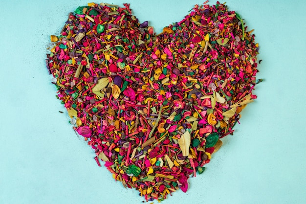 Top view of multicolored dried flower petals blooms and herbs arranged in a heart shape on blue