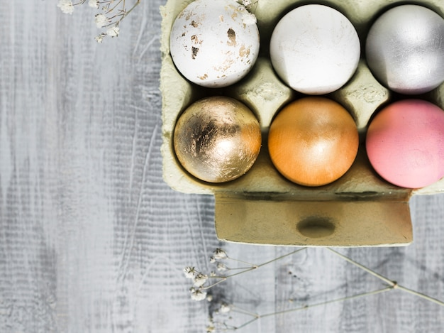 Top view of multicolored easter eggs in carton