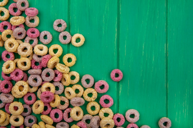 Top view of multicolored loop cereals isolated on green surface