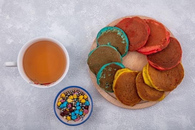 上面図色のチョコレートと白い背景の上のお茶とスタンドの色とりどりのパンケーキ