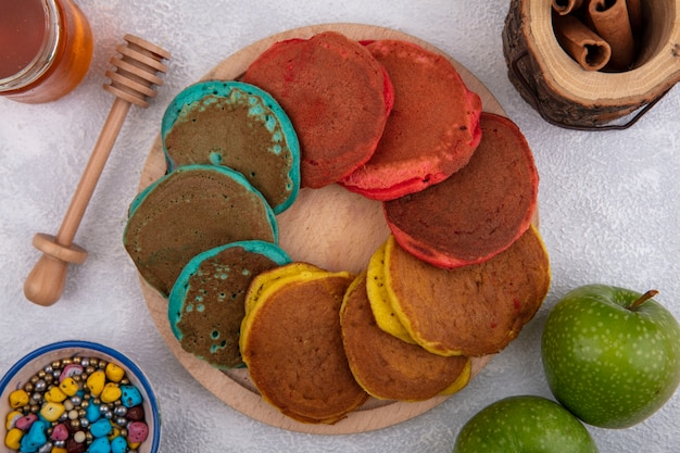 Top view multicolored pancakes on a stand with green apples  colored chocolates  cinnamon and honey on a white background