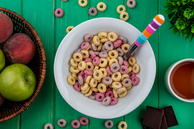 Top view of multicoloured loop cereals on a white bowl with colorful spoon on green surface