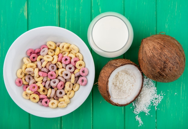 Top view of multicoloured and loop cereals on a white bowl with a glass of milk and coconut on green surface