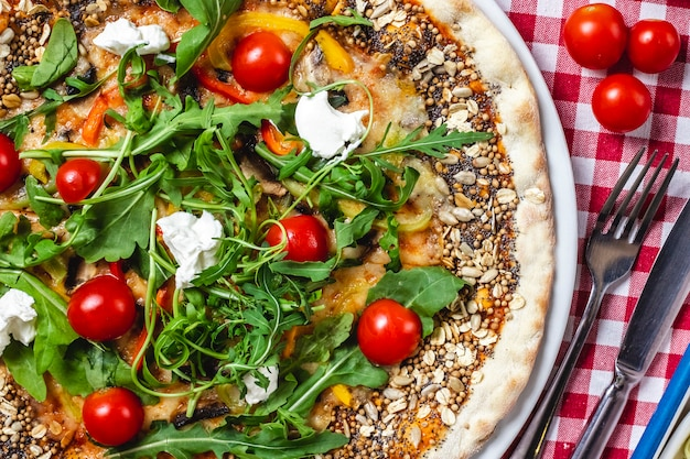 Top view multigrain pizza with fresh cherry tomatoes mozarella cheese bell pepper and arugula on top